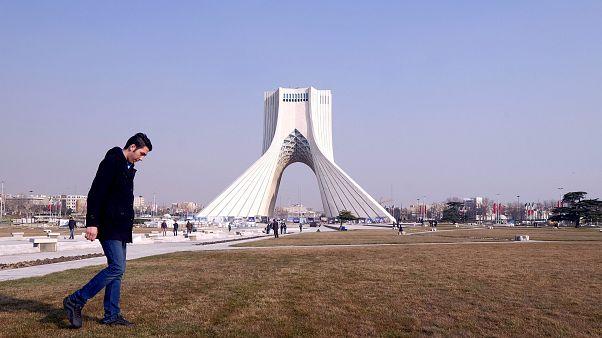 Ein Iraner läuft vor dem Azadi Turm in Teheran