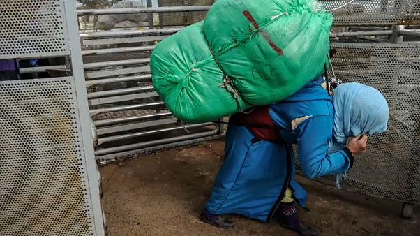 Eine Marokkanerin mit riesigem Lastenbündel auf dem Rücken