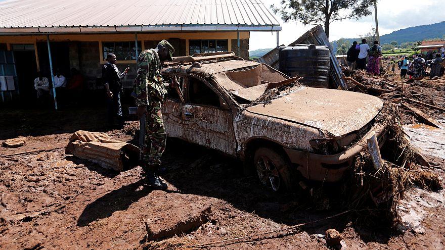 Ein kenianischer Soldat inspiziert ein vom Schlamm erfasstes Auto