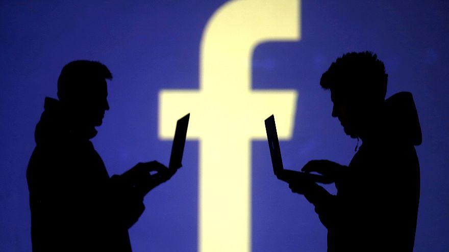 Silhouetten zweier Männer mit Laptop vor Facebook-Logo
