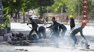 عنصر من الشرطة يساعد صحفي أفغاني بعد تفجير في العاصمة كابول الأسبوع الماضي