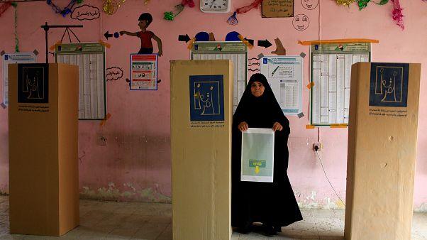 Eine Frau mit Stimmzettel neben den Wahlkabinen im Irak