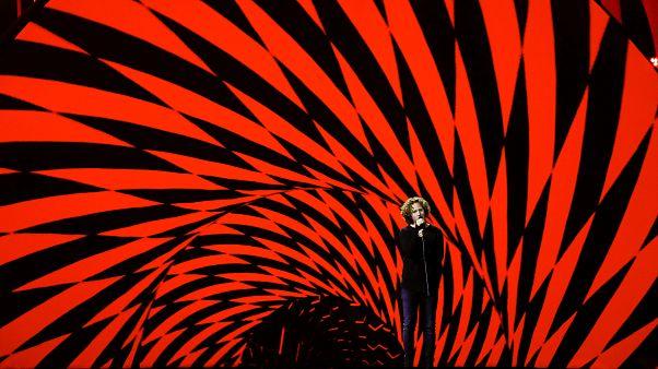 Michael Schulte singt beim ESC-Semifinale vor rot-schwarzem Hintergrund