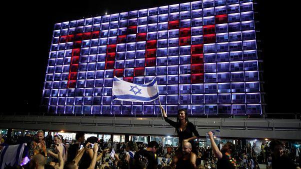TOY-Lichtprojektion auf ein Hotel in Tel Aviv; Israel-Flaggenschwenkerin