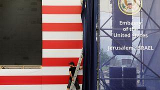 Ein Mann arbeitet vor den Streifen einer USA-Flagge.