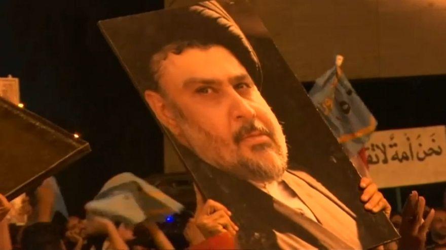 Supporters of Iraqi cleric Moqtada al-Sadr brandish a giant poster