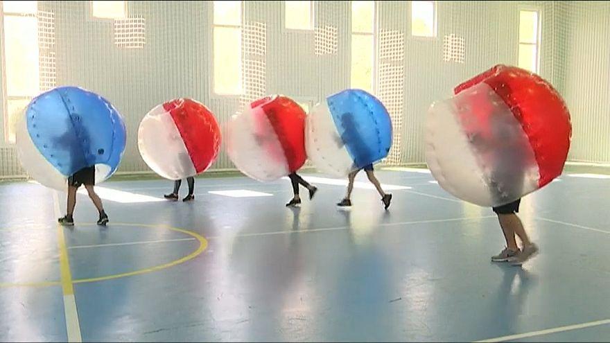 Russian children play fun soccer in bumper balls