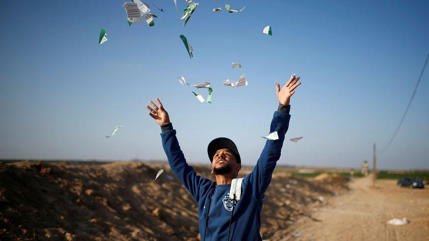 شاب فلسطيني ينثر منشورات مزقها بعد أن ألقاها الجيش الإسرائيلي على قطاع غزة