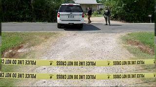 Gelbes Absperrband der US-Polizei, dahinter ein weißes Polizeiauto