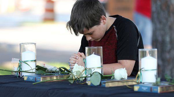 Ein Junge betet, drei weiße Kerzen stehen auf dem Tisch vor ihm.