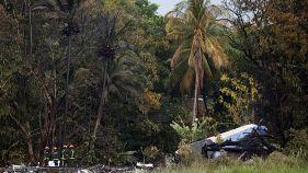 Ein Flugzeugteil liegt vor einem Palmenwald, Feuerwehrleute links