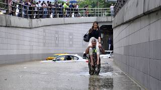 Man carries a woman on his shoulders at a flooded street