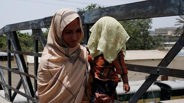 أم تغطي ابنها بمنشفة مبللة لتقيه حر الشمس