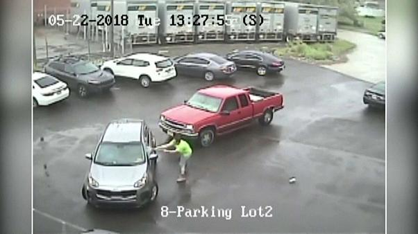 A man attacks a car and passenger with a sledgehammer