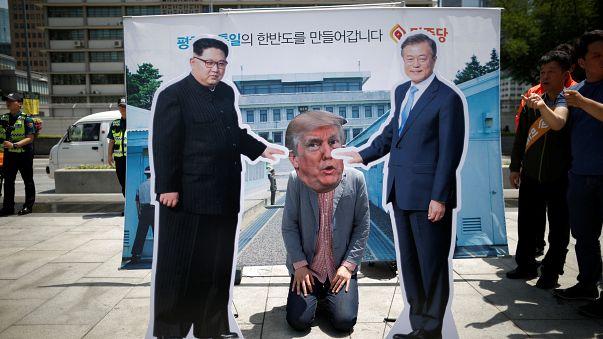 A man wearing a mask of U.S. President Donald Trump kneels down between cut