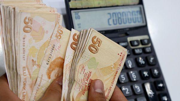 Un cambiavaluta turco conta un fascio di banconote da 50 lire turche