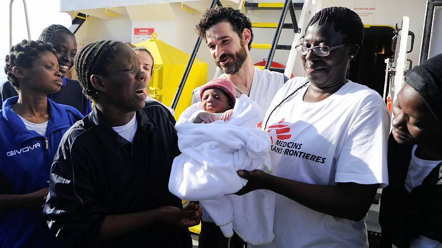 Woman, who just gave birth on board the Aquarius, reacts as she takes her n