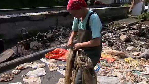 Mulher com plástico retirado do fundo do rio