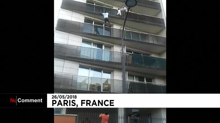 Malian migrant Mamoudou Gassama scales a building to save a young boy