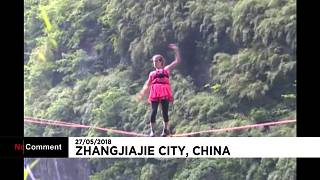 A woman in high-heels walks a highline in China's Hunan province