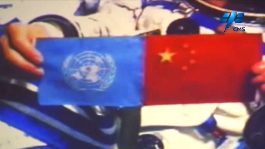 Chinese astronaut holds up the flags of the United Nations and China