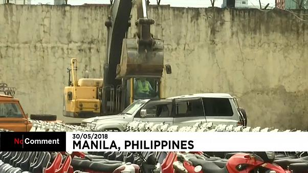 A bulldozer crushes luxury cars in the Philippines