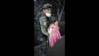 Guatemalan police officer rescuing a baby from the debris
