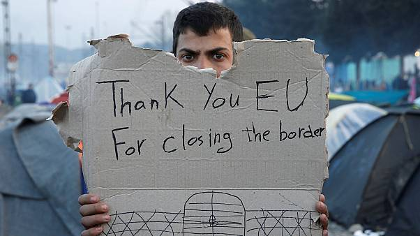 A refguee holds a message at the Greek/Macedonian border