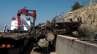 الرافعة تزيل حطام حافلة صغيرة اصطدمت بجدار خرساني في بلدة باليونان - رويترز