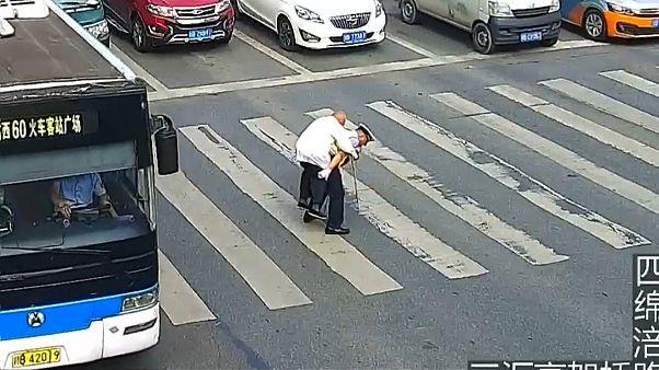 الشرطي حاملاً الرجل المسن على ظهره
