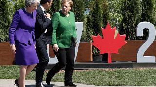 Theresa May (L), Emmanuel Macron and Angela Merkel at the 2018 G7 Summit.