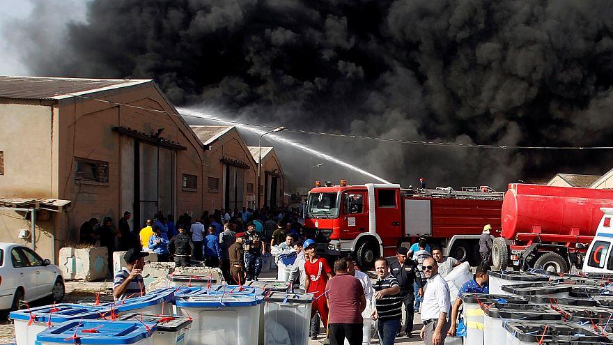 رجال الاطفاء يحاولون إخماد حريق في مخزن لصناديق الاقتراع في بغداد