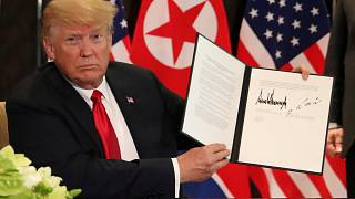 Donald Trump holds up the signed document