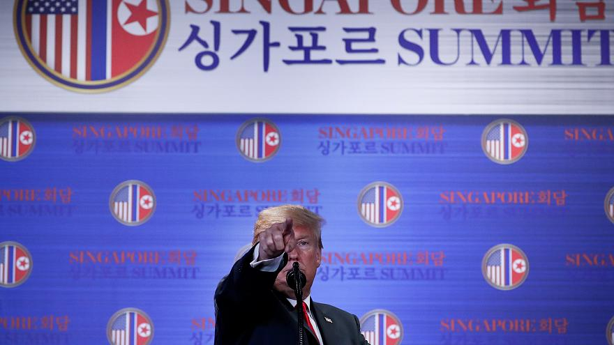 Trump points during a news conference after his summit with Kim Jong-un