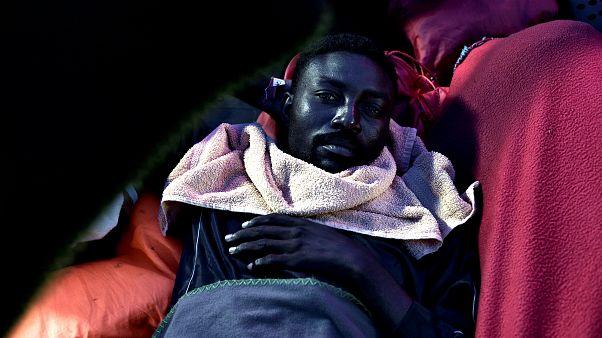 A migrant rests on the deck of MV Aquarius