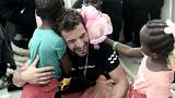 A crew member hugs a migrant child aboard the Aquarius rescue ship