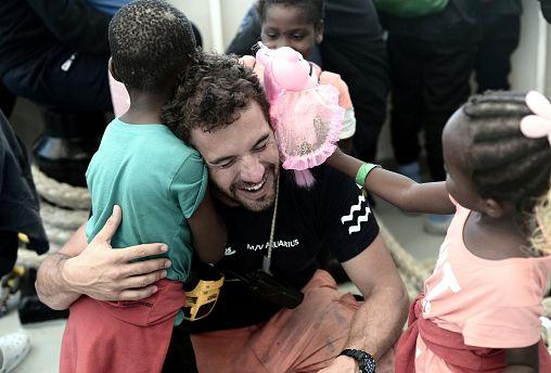 A crew member hugs a migrant child aboard the Aquarius rescue ship