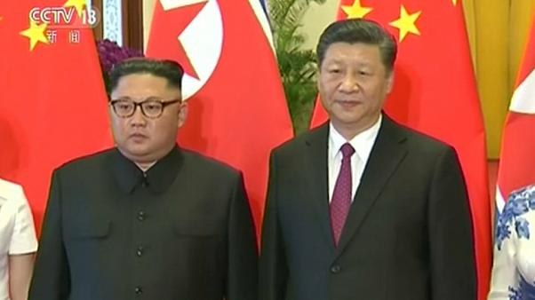 North Korea's Kim Jong-un and China's Xi Jinping stand side by side.
