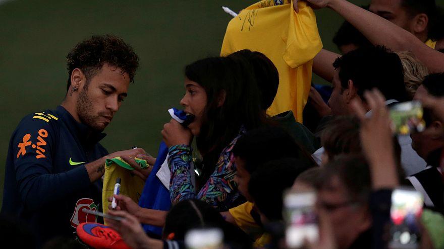 نيمار لاعب منتخب البرازيل يوقع على قميص أحد الجماهير خلال جلسة تدريبية