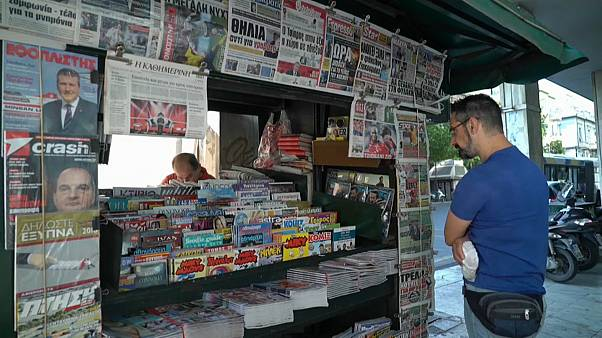 Greek newspapers carrying news of the debt relief deal