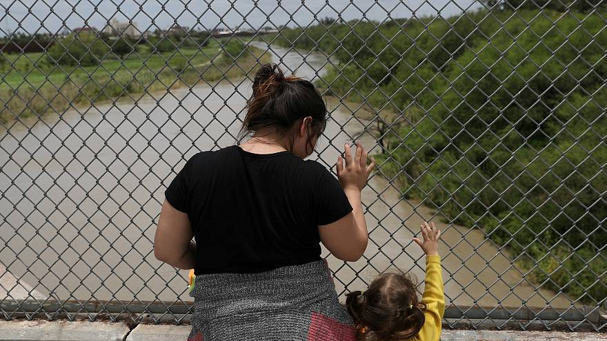 A Honduran mother and daughter seeking asylum wait on the Mexican side of t