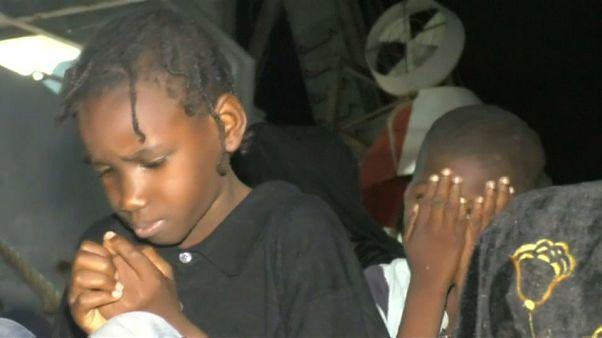 Child migrants sitting on dock in Libya's port of Tripoli