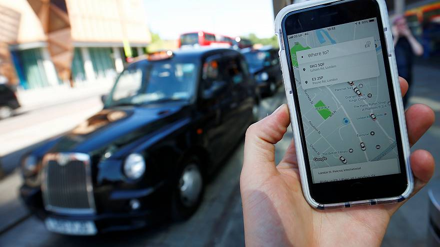 A photo illustration shows Uber app and a black London cab