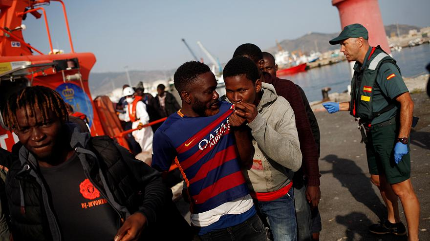 A migrant kisses a Barcelona jersey after arriving on a boat in Motril
