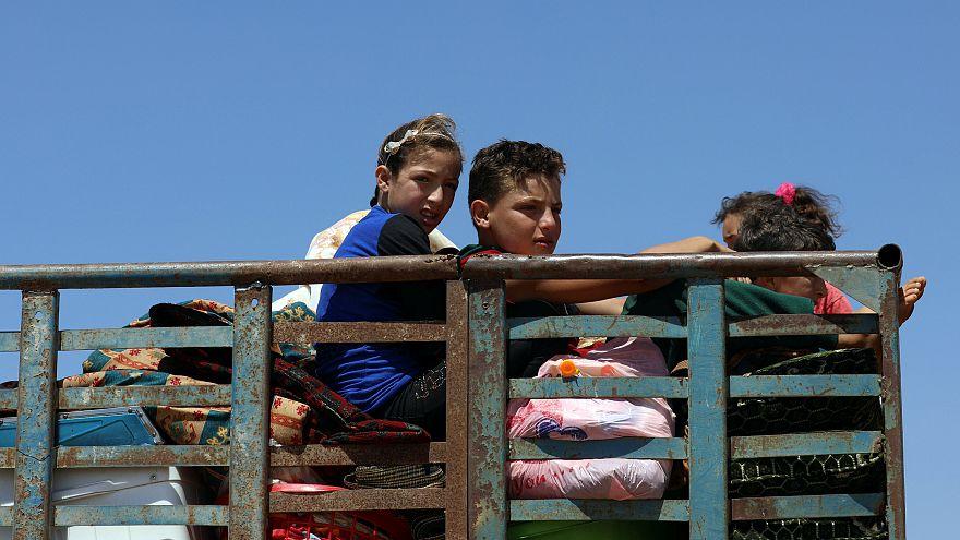 أطفال مع أمتعتهم فارّون من العنف المتصاعد في ريف درعا - علاء الفقير رويترز