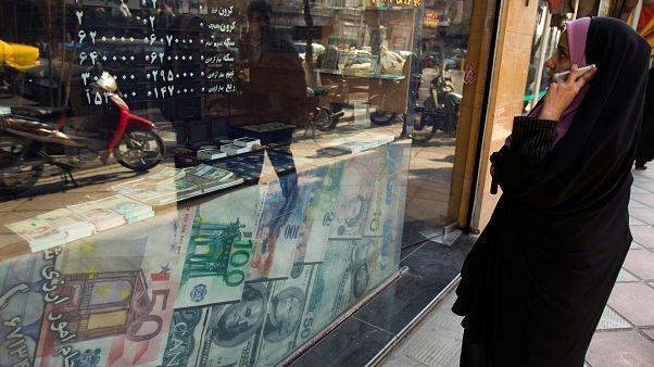 Une femme regarde les taux de change dans une boutique à Téhéran.