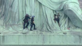 Una mujer escala la Estatua de la Libertad para protestar contra Trump