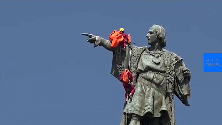 Activists place life jacket on Christopher Columbus statue in Barcelona
