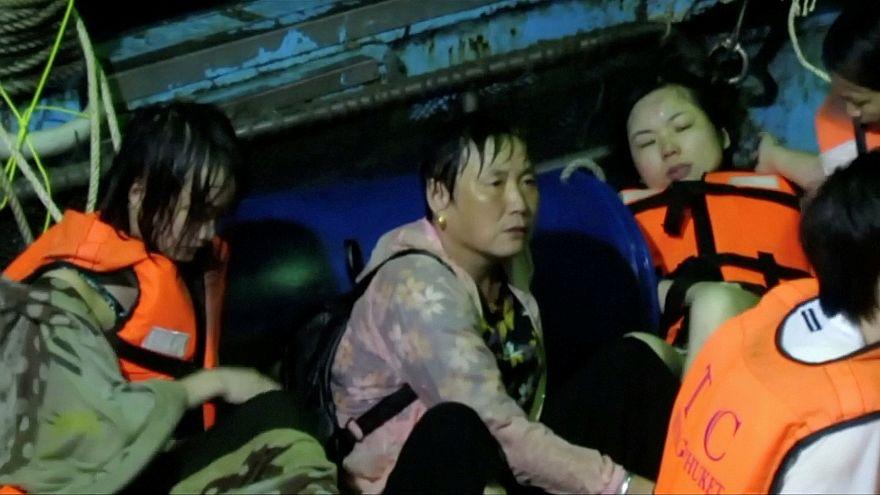أشخاص يجلسون على قارب صيد بعد إنقاذهم إثر غرق قارب كانوا على متنه
