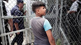 A migrant boy stands next to a fence at the Moria refugee camp on Lesbos.